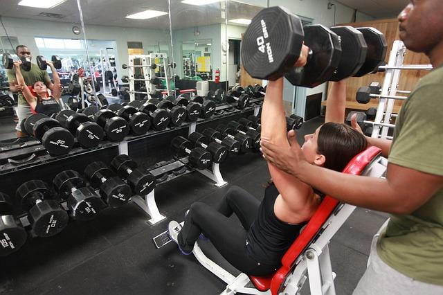 筋トレで肩が大きくならない女性に指導する男性